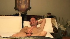 A hot guy is stroking his cock on the bed when his horny neighbor shows up